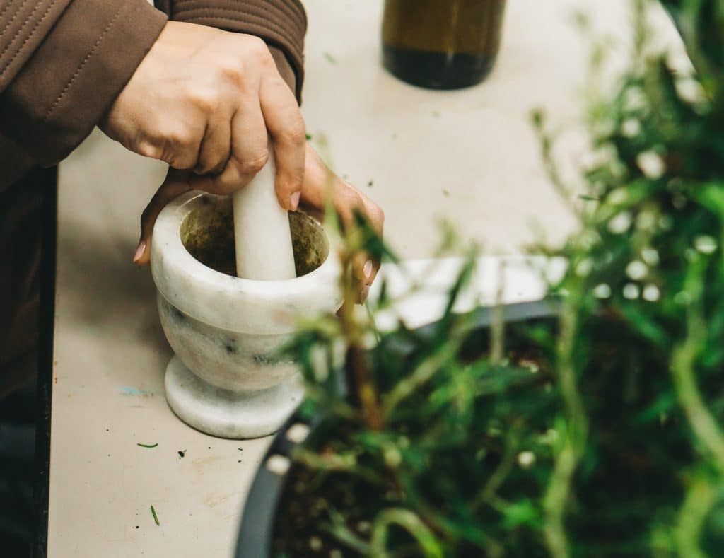 Woman grinding herbs with a mortar and pestle.