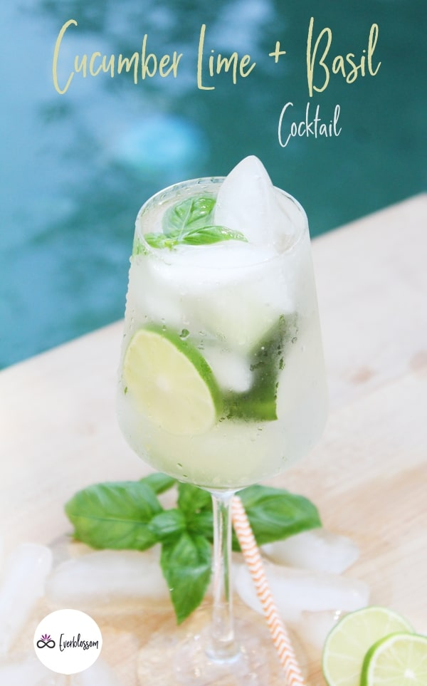 Iced cocktail with limes and basil in a glass.