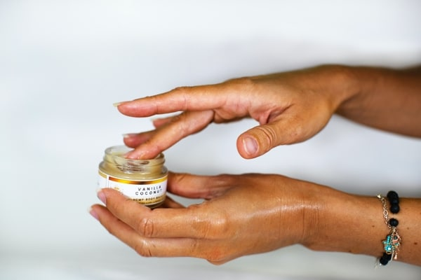One hand is holding an open jar of cleansing balm while the other hand is applying product with fingertips.